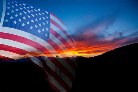 American Flag With Landscape Sunset Background Stock Photo